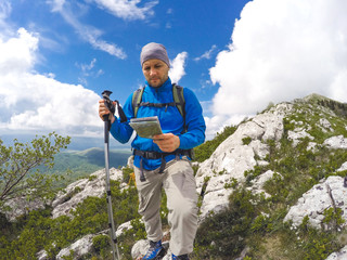 Hiker on top of mountain, lookin at map
