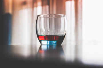 Fototapeta Glass of cognac stands on a table