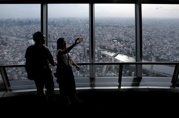 Visitors take selfie photos as the general view of the central Tokyo is on the background at the observation deck of Tokyo Skytree in Tokyo