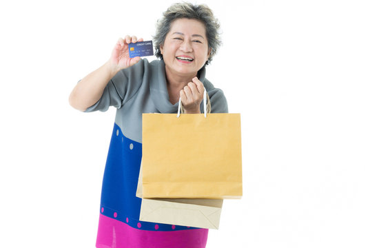 Senior asian female with grey hair smiling holds credit card and shopping bags.