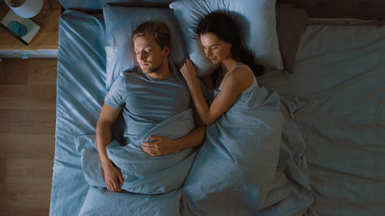 Top View Bed at Night: Attractive young Couple Sleeping Together, Holding Each other in Arms, Embracing. First Rays of Morning Sun Illuminate Room Trough the Window