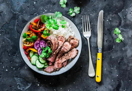 Balanced power buddha bowl - grilled beef steak, roasted and fresh vegetables, rice on a dark background, top view. Healthy diet food concept