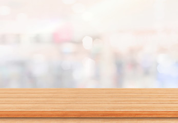 Wall Mural - Empty wood table top on blur abstract background from inside shopping mall. Template mock up for display of product