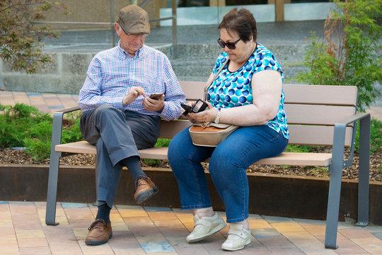 Pareja de personas mayores (abuelos) sentados en un banco del parque mientras miran y comentan mensajes y fotos divertidas recibidas en sus teléfonos móbiles (smartphones) en una tarde soleada de vera