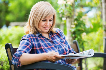 Portrait of  mature woman sitting on bench and reading book in garden