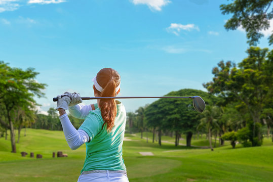Healthy Sport. Asian Sporty woman golfer player doing golf swing tee off on the green evening time, she presumably does exercise.  Healthy Lifestyle Concept..