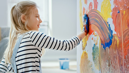 Happy Little Girl with Hands Dipped in Vivid Paint Draws Colorful Abstractions on the Wall. She is Having Fun and Laughs. Home is Being Renovated.