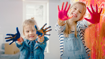 Two Fun Little Sisters Show Their Hands that are Dipped in Colorful Paint. They are Happy and Laugh. Sisterhood Goals. Redecoration at Home.