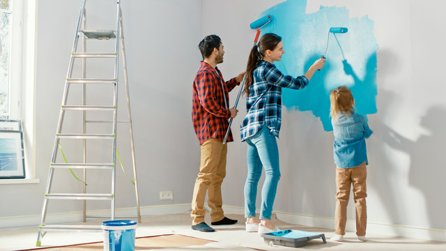 Family Time Together with Small Daughter. Young Father and Mother Showing Their Child How to Paint a Wall with a Roller. Paint Color is Light Blue. Room at Home is Prepared for Renovations.