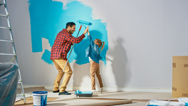 Young Father is Showing How to Paint Walls to Cute Small Daughter. They Give High Give to Each other. Rollers are Covered in Light Blue Paint. Room Renovations at Home.