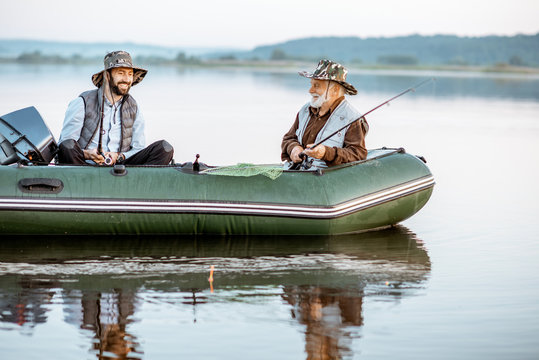 Grandfather with adult son fishing on the inflatable boat on the lake early in the morning