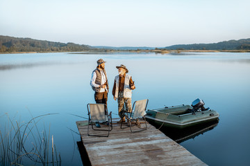 Grandfather with adult son standing together on the wooden pier, enjoying the sunrise while fishing on the lake early in the morning