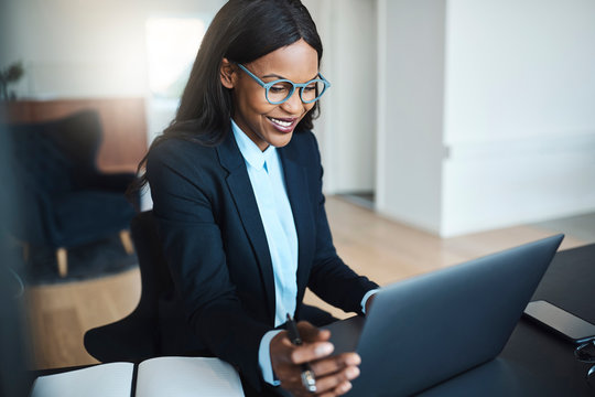 Young African American businesswoman smiling while working at he