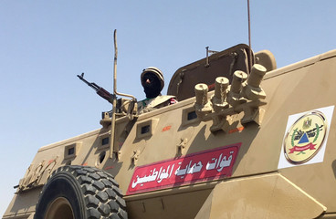 Soldier monitors above a military vehicle patrol in Cairo