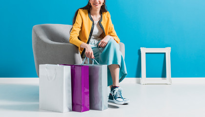 Wall Mural - Happy woman sitting on an armchair after shopping