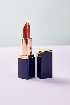 single opened tube of red lipstick on purple