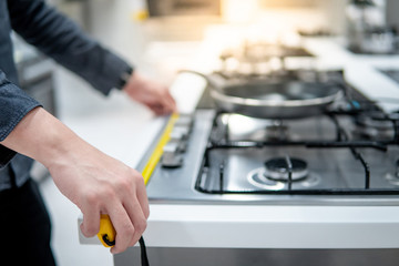 Male hand interior designer using tape measure on gas stove on modern countertop in kitchen showroom. Shopping appliance for domestic kitchen. Home improvement concept