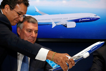 Ihssane Mounir moves a model of Boeing 737 MAX next to Kevin McAllister, Boeing Commercial Airplanes CEO, during the 737 MAX 8 commercial announcement at the 53rd International Paris Air Show at Le Bourget Airport near Paris