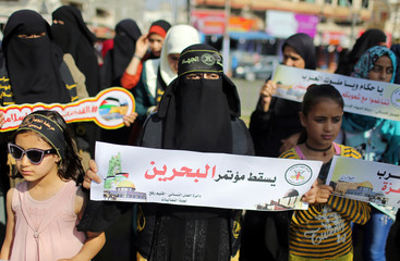 """Palestinian woman holds a sign reading """"down with the Bahrain conference"""" during a protest against Bahrain's workshop for U.S. peace plan, in the southern Gaza Strip"""