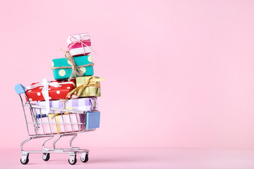 Small shopping cart with gift boxes on pink background