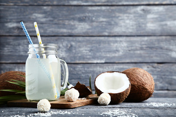 Wall Mural - Coconut water in jar with candies on wooden table