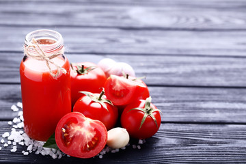 Wall Mural - Tomato juice in glass bottle with garlic and salt on wooden table