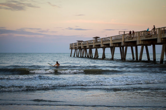 People surfing by pier in the sunset