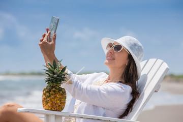 Beautiful woman taking selfies at a paradisiac tropical beach