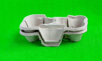 Two paper cups with takeaway drinks. Isolated on green background.Pressed cardboard paper double cup holder
