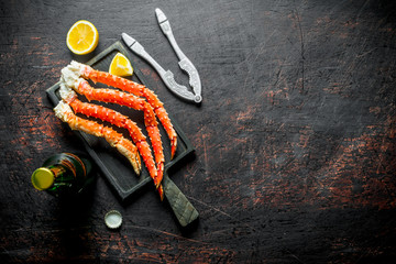 Crab on a cutting Board with a bottle of beer and slices of lemon.