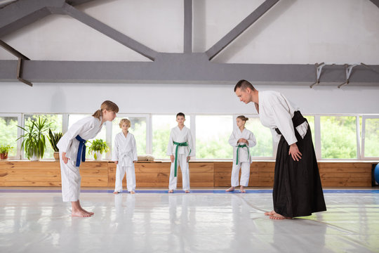Girl giving a bow to trainer before practicing aikido