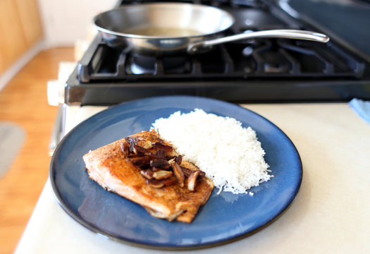 Plate of steelhead trout with chopped garlic and rice.