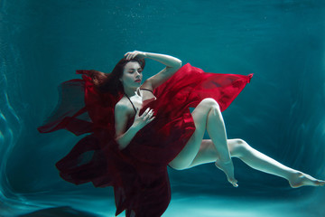 beautiful girl in a red dress dive into the water.