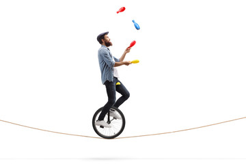 Male juggler with clubs riding a unicycle on a rope Wall mural