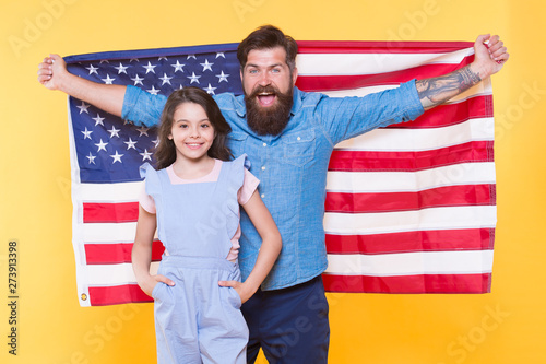 Celebrating the Independence every July 4th. Happy family commemorating anniversary of nations independence. Father and little child holding american flag on Independence day. Happy Independence day
