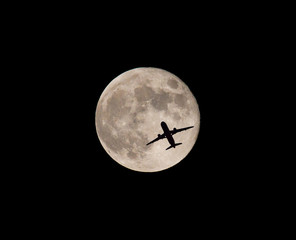 Commercial Airliner Silhouetted by Full Moon