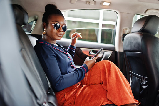 Rich business african woman on sunglasses sit at suv car with black leather seats. Mobile phone at hand.
