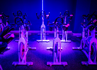 An indoor cycling dance class in a blue LED lighting room