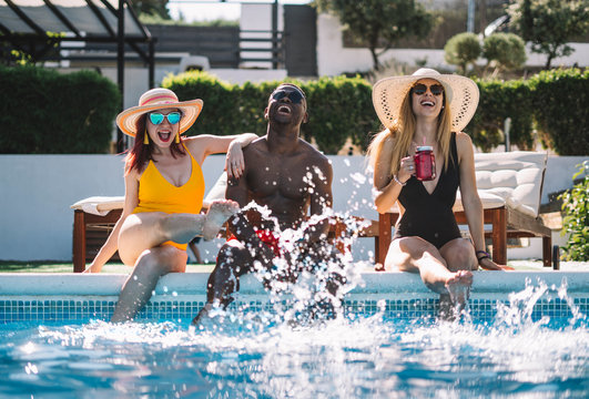 Two happy women and a man sitting at the pool splashing with water