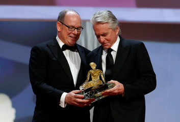 Prince Albert II of Monaco reacts with actor Michael Douglas who is being honoured with the Crystal Nymph award during the closing ceremony of the 59th Monte-Carlo Television Festival in Monaco