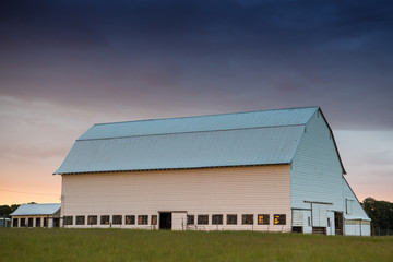 White barn at sunset in a green, grassy field under a sky with purple, yellow, and orange clouds - Willamette Valley, Oregon