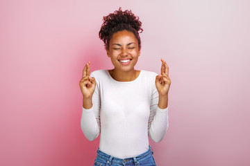 Cute mulatto woman crossing her fingers and wishing for good luck - Image
