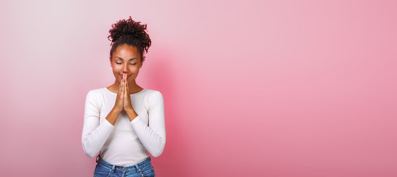 Portrait of woman in supplication pose with smile and close eyes over pink background. Copyspace