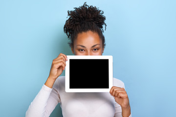 Mockup image of black empty blank screen of ipad in the female hand, peeking from behind tablet over blue background