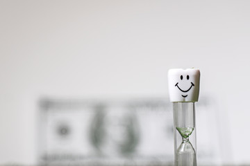 Tooth,dollar and hourglass on a white background.