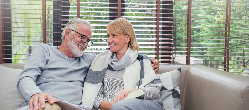 Portrait of happy old couple smiling in living room at home, caucasian senior couple relax in sofa. Healthcare lifestyle elderly retirement together true love concept panoramic banner