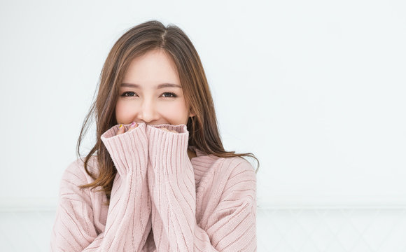 Portrait of young beautiful asian woman relax in bedroom. Smile happy asian girl hands cover face wear winter cloth. Beauty perfect clear skin japanese makeup  lifestyle concept panoramic banner