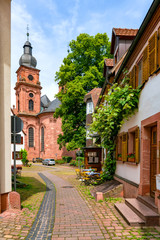 Narrow street with view of the church in the old town of Amorbach in Lower Franconia, Bavaria, Germany