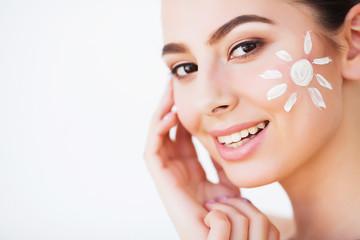 Sun Tanning. Beauty Girl Applying Sun Tan Cream on her Face. Fotoväggar