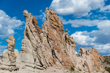 Unusual, craggy rock formations and rugged pinnacles under a beautiful blue sky with white puffy clouds - Plaza Blanca near Abiquiu, New Mexico